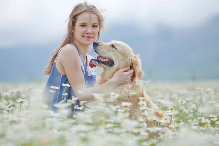 Pretty girl with her dog in a field